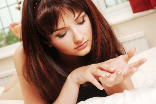 A beautiful young woman in bed looking at her hands.